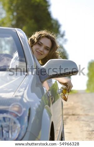 Young woman is sitting in a car with sunglasses in a hand and smiling