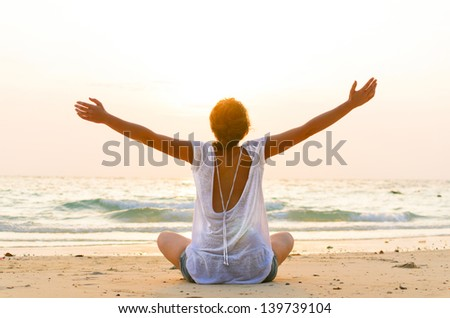 young woman is sitting on beach at sunrise