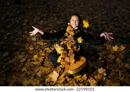 young woman is sitting with a guitar and flying leaves