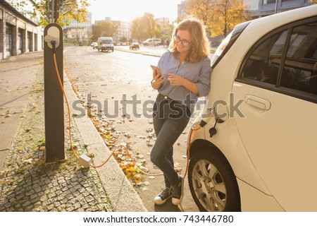 Young woman is standing near the electric car and looks at the smart phone. The rental car is charging at the charging station for electric vehicles. Car sharing.
