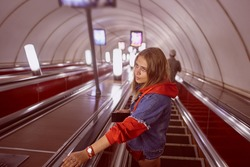 Young woman is standing on the stairs of escalator which is descending to the underground metro station.