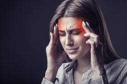 Young woman is suffering from a headache against a dark background. Studio shot