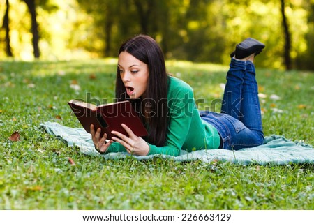Young woman is surprised about something she had read in a book,Surprised woman