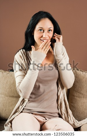Young woman is talking on the phone and hearing surprise news,Surprised woman