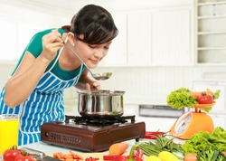 young woman is tasting her cooking in the kitchen