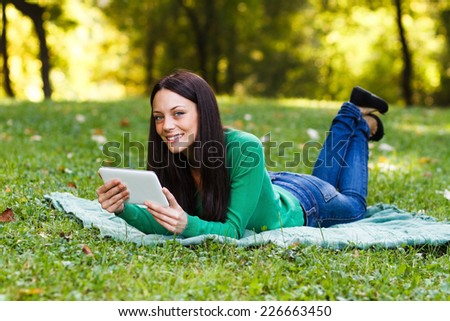 Young woman is using her digital tablet while lying down in the nature,Woman using digital tablet