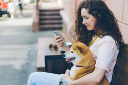 Young woman is using smartphone enjoying social media with dog in street cafe sitting on wooden bench holding device hugging animal. People and pets concept.