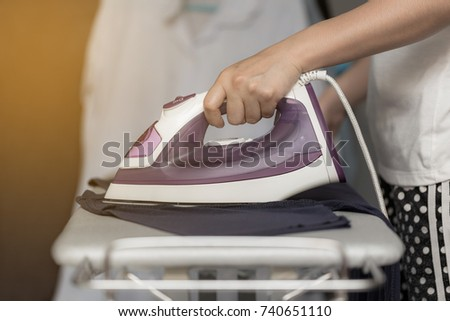 Young woman is using steam iron on her cloths #740651110