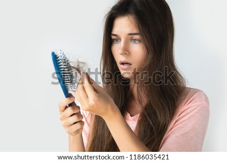 Young woman is very upset because of hair loss