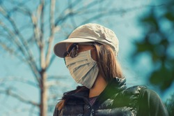 Young woman is wearing handmade textile protective face mask during coronavirus pandemic