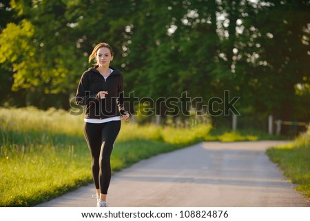 Young woman jogging in park at morning. Health and fitness.