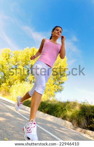 young woman jogging/jumping on road - stock photo