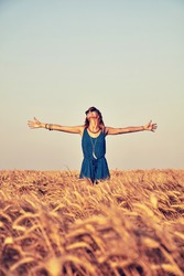 Young woman jumping and enjoying in a wheat field.