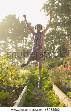 Young woman jumping for joy in a garden