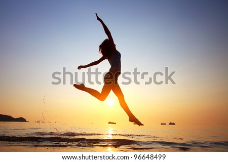 Young woman jumping in a water on a beach