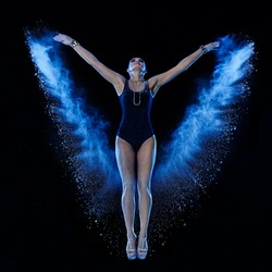 Young woman jumping in blue powder cloud on black background