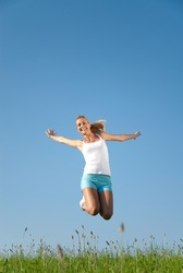 young woman jumping in the air in front of a blue sky