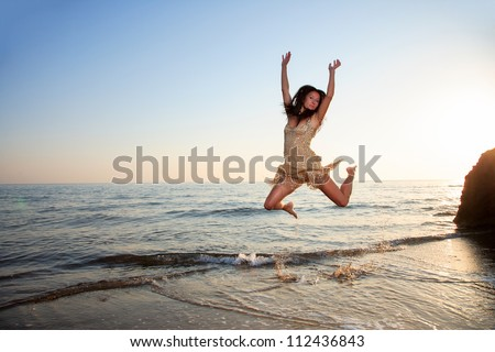 Young woman jumping on a beach in the summertime