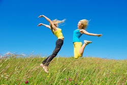 young woman jumping on background green meadow and blue sky