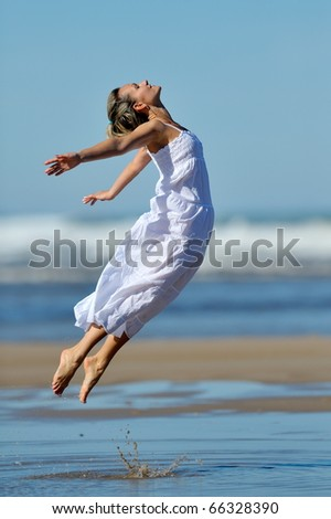 young woman jumping on the beach in summer