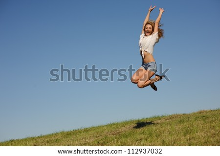 Young woman jumping on the green summer field