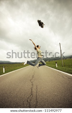 Young woman jumping  on the long empty street.