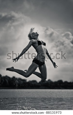 young woman jumping out of water.black and white