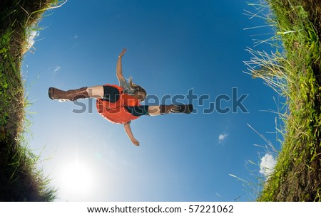 young woman jumping over a creek; shot from below - stock photo