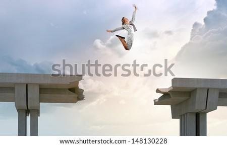 Young woman jumping over a gap in the bridge as a symbol of risk - stock photo