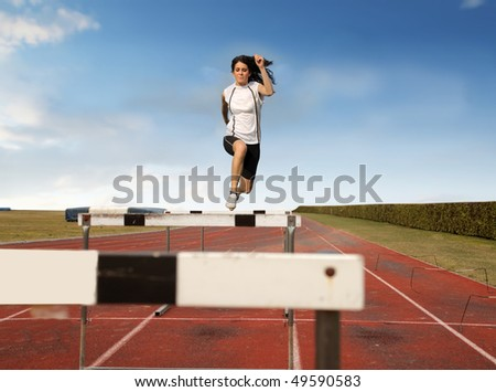 Young woman jumping over an obstacle on a running track