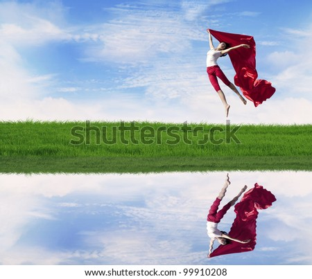 Young woman jumping with red scarf on the meadow with water reflection