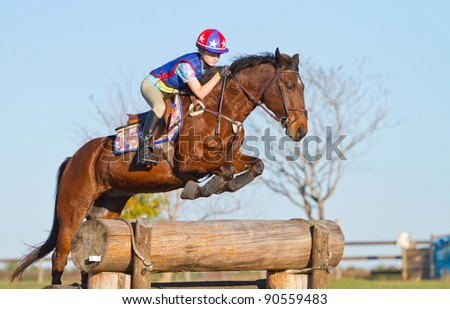 Young woman jumps a horse during practice on a cross country eventing course