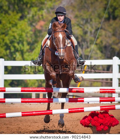 Young woman jumps high during a show jumping event