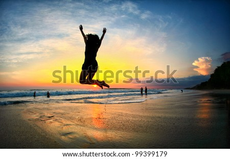 Young Woman Jumps on Beach at sunset in Costa Rica - stock photo