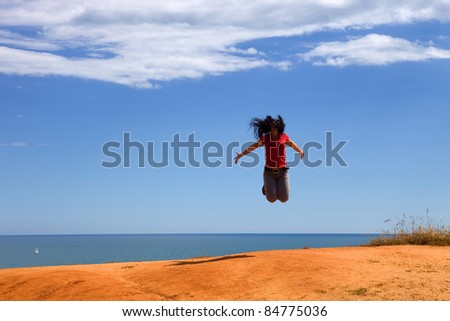 young woman jumps with arms wide open at the coast