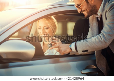 Young woman just buy a new car.Sales man giving a key for a new car.
