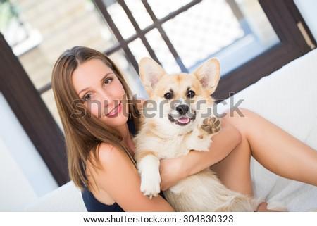 Young woman keeping welsh corgi  puppy  near her face