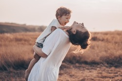 Young woman kisses her little son at sunny in the meadow in sunset. Young mother holding her baby. Mother and  little son having good time in the nature. Color toned image. Mothers Day. Family Concept