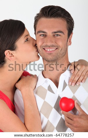 Young woman kissing a man on the cheek