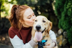 Young Woman kissing Golden Retriever Dog