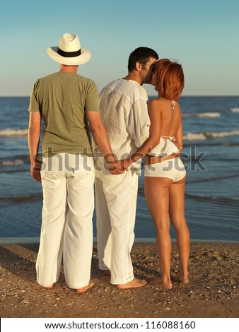 young woman kissing one man and holding hands with another, by the sea shore