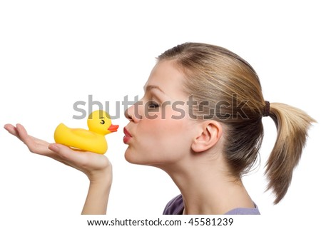 young woman kissing the yellow rubber duck on her hand