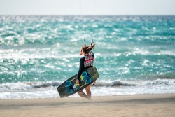 Young woman kitesurfer on the beach entering the sea with her board. Sotavento beach in Fuerteventura