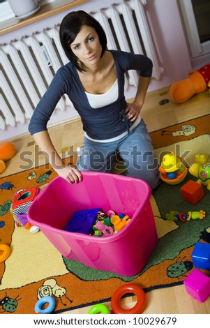 Young woman kneeling at container with toys and assembles strewn toys. High angle view.