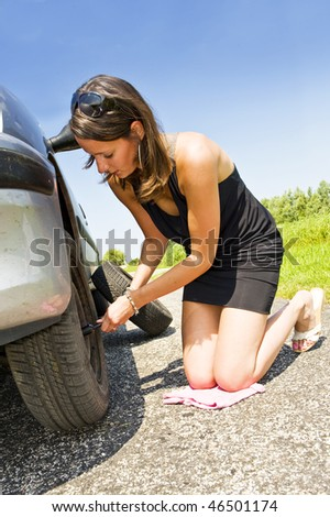 Young woman kneeling, changing the front tire of her car