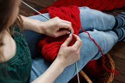 Young woman knitting red muffler at home in leisure time, fancywork and needlework concept, closeup of hand work, copy space, from above overhead view