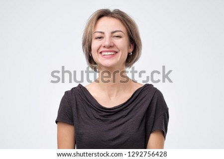 Young woman laughing on gray background on funny joke of her boyfriend. #1292756428
