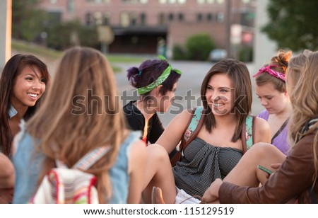 Young woman laughing with her friends sitting outside