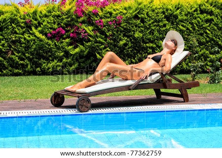 Young woman laying by the swimming pool during her vacation