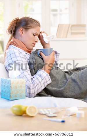 Young woman laying in bed, caught cold, feeling bad, drinking tea, taking vitamins.? - stock photo